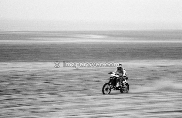 Enduro du Touquet 1986. Dirt bike beach race at Le Touquet, Normandy, France. --- No releases available, but releases may not be necessary for certain uses. Automotive trademarks are the property of the trademark holder, authorization may be needed for some uses. --- Info: A thousand motorcycles take part in this mad event. The race starts along the beach, followed by a run into the sand dunes. The entry point in the dunes is most spectacular: All motorbikes have to pass through a small opening in the dunes. Once the fast professional drivers have flown through, this first passage developes into a true bottleneck with many hundreds of motorbikers trying to get through at the same time. Motorcycles are strewn all over the place. Many have fallen, others have already broken down. In the meantime, the professional riders are progressing quickly. But their riding style changes from racing full-out as soon as they are approaching the lappers from behind. Outmaneuvering them at high speeds is an art form! After three hours it's all over.....