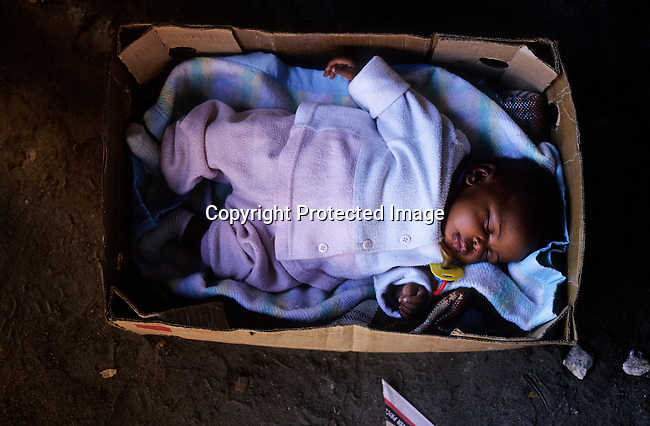 Sibobalwe Miwonyelano, age 5 months, sleeps in a cardboard box while her mother sell sheep heads at a roadside market on October 12, 2003 at Town 2 section in Khayelitsha, a poor township outside Cape Town, South Africa. The mother is trying to make ends meet by selling boiled sheep heads, a traditional Xhosa dish, for about 2 US$ apiece. It's estimated that over one million people live here, most of them under appalling conditions in shacks with no running water or electricity. (Photo by: Per-Anders Pettersson).