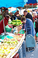 Vegetables and fruits for sale at a market stall at the street market in Bergerac, an old woman with a shopping cart buying vegetables. Bergerac Dordogne France