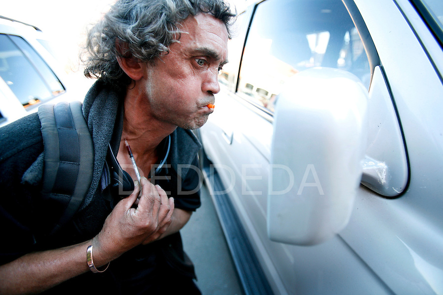 A local drug addict named Ricky uses a parked vehicle's side mirror to inject a used needle containing blood and left-over drugs from previous users, which he found on the ground, into a vein in his neck, at one of the main shooting galleries for intravenous drug-users in downtown Victoria, British Columbia, BC, Canada. Photo shot for the NATIONAL POST.