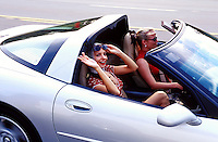 A smiling young woman waves as she and a friend ride in a silver Corvette.