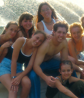 A group of teenagers have fun by an outdoor fountain.