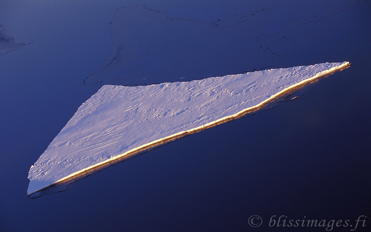 A solitary ice floe floats in the archipelago shipping channel between Sweden and Finland.