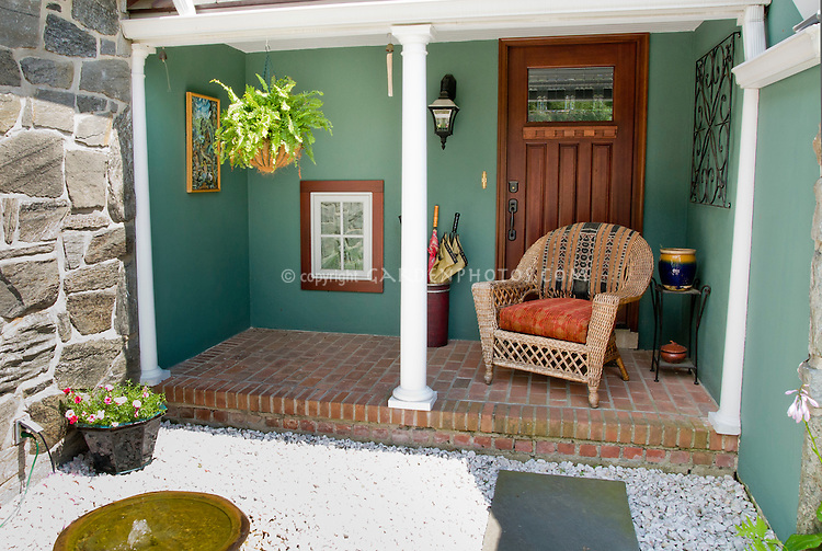 Outdoor room porch with wicker chair, hanging Boston fern houseplant, painting, container plants, little water fountain feature, rock stone mulch, brick patio, beautiful wooden door, ornaments, flea market finds, old window mirror, to make a charming retreat garden.