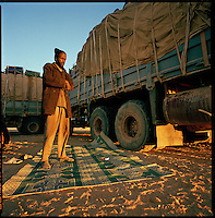 Sahara desert, Libya-Chad, November/December 2004..Every week, a convoy of 40 privately owned Libyan trucks loaded by the WFP with about 1000 metric tons of western food aid cross 2500 km of deep desert across Libya and Chad to reach more than 200 000 refugees from Darfur in camps near the Sudanese border. Early morning prayer.