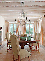 The combination of rustic materials and neutral colours creates a cool ambience as in the light and airy dining room. A wire chandelier hangs above the solid wood table and chairs.