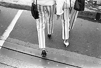 Two woman crossing the street, dressed in stripes pants