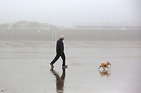 A lone man walks his dog in fog at Aberavon Beach, Port Talbot, Wales, UK. Monday 13 March 2017