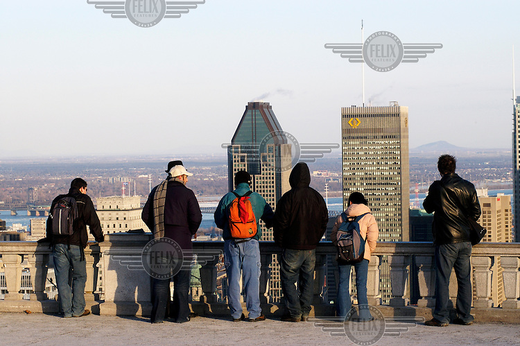 People on the terrace of the White Chalet in Mont Royal Park which has a view over the downtown area.