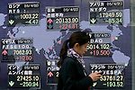 A woman passes next to the stock market indicator board on April 22, 2015, Tokyo, Japan. The Japan stock market broke 20,000 yen during the morning trading session of the Tokyo Stock Exchange. (Photo by Rodrigo Reyes Marin/AFLO)