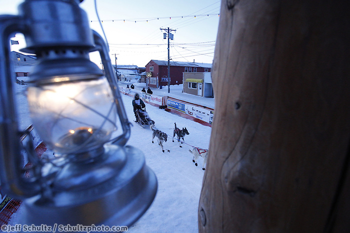 The Widows Lamp, lit until the last musher reaches Nome hangs from the burled finish line arch in as Paige Drobny runs down the finish line in 34th place on Thursday March 14, 2013. Iditarod Sled Dog Race 2013..Photo by Jeff Schultz copyright 2013 DO NOT REPRODUCE WITHOUT PERMISSION