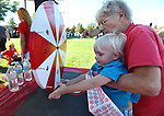 Target volunteer Kathleen Branham helps Sebastian Fuchslin, 2, spin the wheel for a prize during the 14th annual National Night Out in Carson City, Nev., on Tuesday, Aug. 2, 2016. <br />