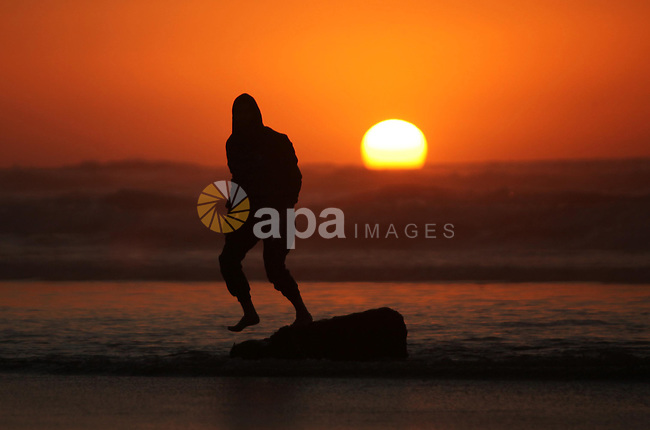 A Palestinian man walks on the beach of Gaza City, during the last sunset of 2016, on December 31, 2016. Photo by Ashraf Amra