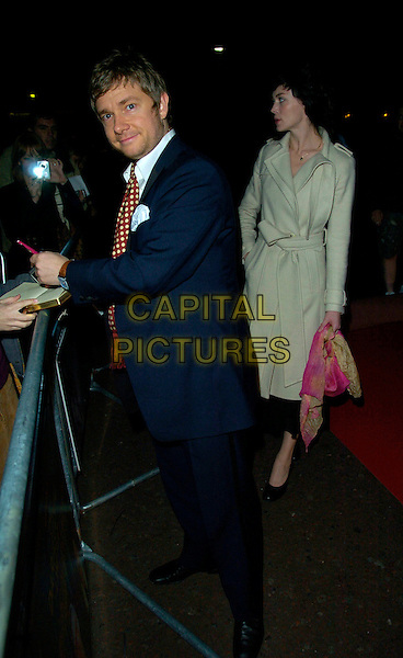 """MARTIN FREEMAN & GUEST.""""The Darjeeling Limited""""  BFI London Film Festival closing gala, Odeon Leicester Square, London, England..November 1st, 2007.LFF full length blue suit signing autograph beige mac.CAP/CAN.©Can Nguyen/Capital Pictures"""