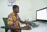 Ebenezer, a graphic designer, works on a layout for business cards. Accra New Town.