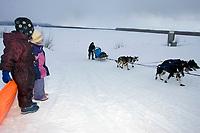 Children Watch Jessica Hendricks Run Up Riverbank into Kaltag Chkpt 2005 Iditarod