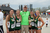 The Mountain Vista girls distance medley relay team pose with their trophy and coach Jon Dalby after winning the event in 12:24, just 34/100ths of a second ahead of second place at the 2015 Kansas Relays.