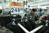 A man shops for jackets, priced at about $30 U.S. dollars, in the Beijing Wal-Mart in Beijing, China on November 6, 2005.