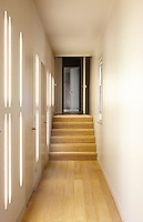 An entrance hallway with netural walls and wooden floor with steps leading up to the front door of an apartment.
