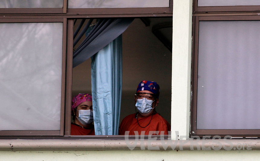 MEDELLIN, COLOMBIA-MAY 29: Two nurses with face masks look out the window of the health center in the neighborhood of Santa Cruz in Medellín, Colombia, on May 29, 2020.The mayor of Medellín and the private company offer a mask facial, antibacterial gel and alcohol for city communes As a preventive measure against the new coronavirus COVID-19. (Photo by Fredy Builes / VIEWpress via Getty Images)