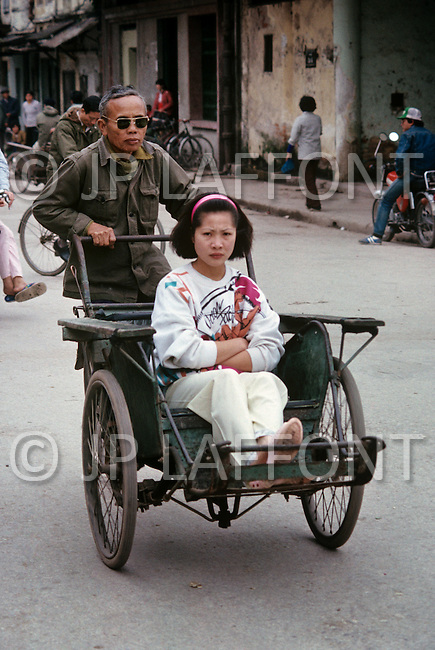 Hanoi, February 1988. Rickshaw at work or at rest in Hanoi City Streets.