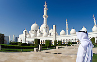 Muslimm Emirates man in white dishelash at the beautiful white Sheikh Zayed Grand Mosque in Abu Dhabi in the UAE the worlds 8th largest Muslim mosque in the world