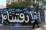 "A Palestinian man walks past a graffiti reading in Arabic ''Division'' in Gaza City, on September 17, 2017, after Hamas announced it had agreed to steps toward resolving a decade-long split with the Fatah movement and was ready to hold elections. Hamas said it had agreed to key demands made by Fatah: dissolving the so-called ""administrative committee"", while saying it was ready for elections and negotiations toward a unity government. Photo by Mohammed Asad"