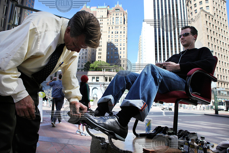 A shoe shiner with a client in the financial centre of San Francisco, California.