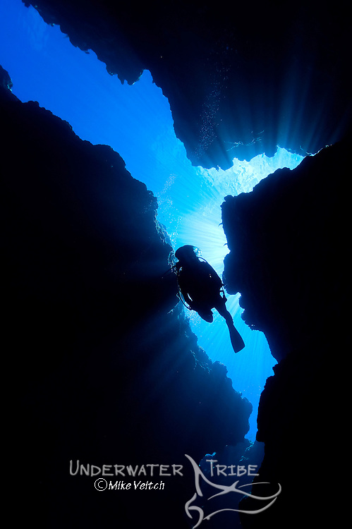 A diver silhouetted by sunlight filtering through cavern system, Yap Caverns, Yap, Federated States of Micronesia, Pacific Ocean
