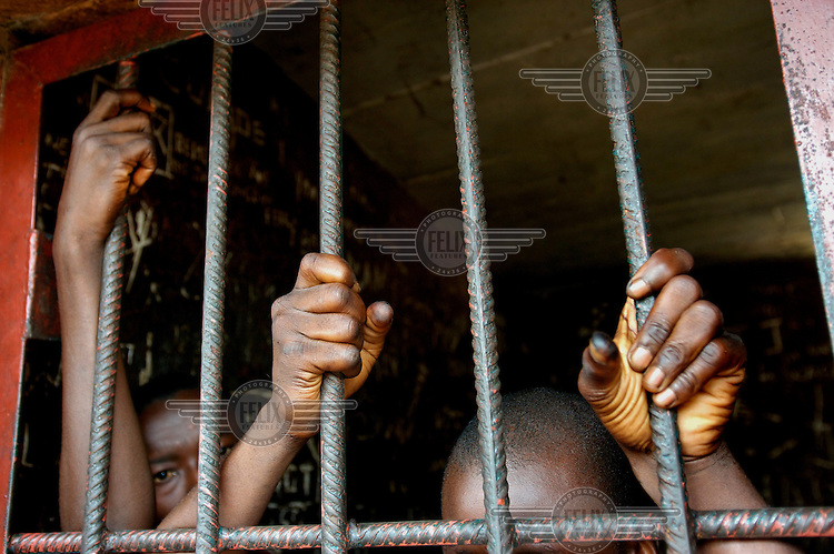 Young men detained in the cells at Bo central police station, partially obscured by, and gripping, the bars of the cell door.