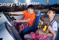 NWA Democrat-Gazette/BEN GOFF -- 04/26/15 Alex Reynolds (from left), 9, of Elkins, tries his hand driving a bass boat in the Walmart FLW Simulator as his sister DeAnna Reynolds, 4, and friend Tyson Seyer, 10, of Centerton watch while visiting the FLW Expo at the John Q. Hammons Center in Rogers on Sunday Apr. 26, 2015.