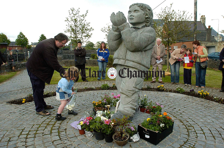 Gerard Backes helps Erin with some flowers during a mass at the Remembrance Garden, Cloughleigh Ennis organised by the Bereaved Parents Association. Photograph by John Kelly.