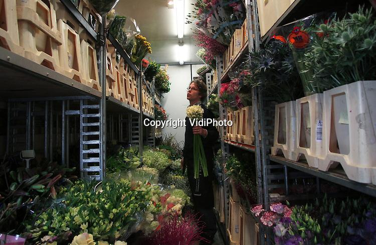Foto: VidiPhoto..VEENENDAAL - Bloemist Peter van de Meent uit Veenendaal shopt maandag in de vrachtwagen van Bloemengroothandel Drost uit Otterlo. Zo vlak voor Valentijn wordt er extra ingekocht. Steeds meer Nederlandse bloemisten kopen via zogenoemde lijnrijders in plaats dat ze zelf bij de Cash & Carry-bedrijven hun inkopen doen. Dat bespaart tijd en bovendien komen de bloemen direct van de 'klok'. Door de naderende Valentijn en de toegenomen vraag naar bloemen, is een bloemetje nu flink duurder dan normaal.