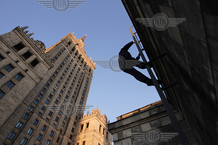 A maintenance worker scales the high walls of the of Soviet-built Palace of Culture.