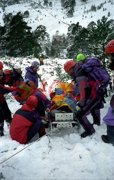 Mountain search and rescue team having found a walker that was seriously injured on a mountainside in snowy conditions.  The casualty has been  covered by a ripstop waterproof nylon cover to protect him from the weather. The team paramedic is assessing the casualty for injuries whislt the stretcher is being lowered down the steep ground. It is supported by the team members and belayed by rope to the tree behind...© SHOUT. THIS PICTURE MUST ONLY BE USED TO ILLUSTRATE THE EMERGENCY SERVICES IN A POSITIVE MANNER. CONTACT JOHN CALLAN. Exact date unknown.john@shoutpictures.com.www.shoutpictures.com...