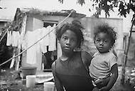 A young girl holds her baby sister in a small town in Belize.