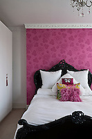 The focus of this bedroom is a wall which has been covered in a bright pink floral wallpaper