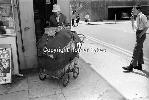 Tower Hamlets east London. Skinhead boy or bovver boy in braces and boots looks on at man with his belongings stacked into a pram. 1978.<br />