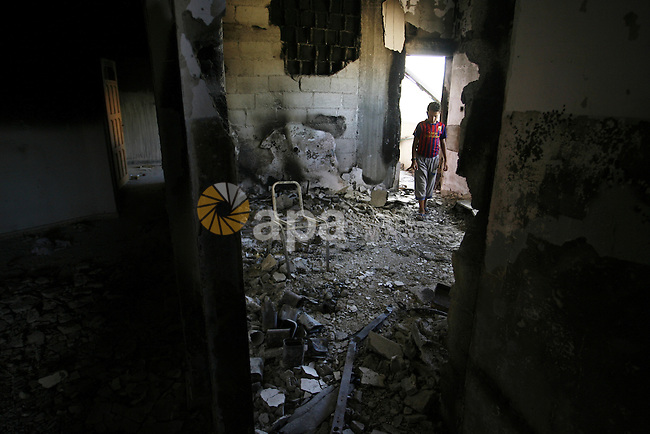 "A Palestinian boy searches in a destroyed house in Khan Yunis in the southern Gaza Strip on September 11, 2014. Israel's deputy foreign minister,Tzahi Hanegbi , warned that Hamas was likely to resume ""violence"" if it feels it has made no political gains from upcoming talks in Cairo. Photo by Abed Rahim Khatib"