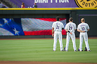 (L-R) Nick Basto (21), Hunter Jones (29), and Mason Robbins (10) stand for the National Anthem prior to the game against the Myrtle Beach Pelicans at BB&T Ballpark on July 7, 2016 in Winston-Salem, North Carolina.  The Dash defeated the Pelicans 13-9.  (Brian Westerholt/Four Seam Images)