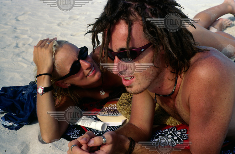 A Western couple wearing sunglasses sunbathe on the beach.