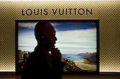 A Chinese man speaks on the mobile phone while walking past a Louis Vuitton signage in a shopping centre in Central Macau, China.