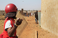Close quarters fighting between the Red Ants and a community of people defending their homes illegally built on private land. A member of the Red Ants confronts a man holding a machette during a so-called 'demolition' operation to clear dwellings and evict squatters from land in Vlakfontein. The violent action resulted in the deaths of two people from among the community being evicted. The Red Ants are a controversial private security company often hired to clear squatters from land and so-called 'hijacked' properties.