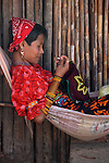 A young Kuna woman in traditional dress in a hammock working on a piece of Mola, a fabric with traditional designed colour and pattern in Playon Chico village. San Blas Archpielago. Panama