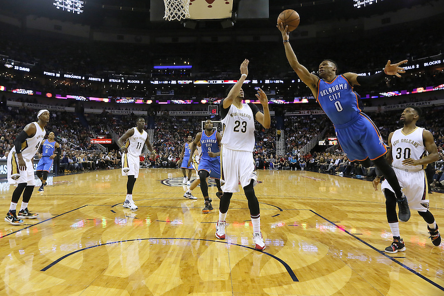 Oklahoma City Thunder guard Russell Westbrook (0) shoots over New Orleans Pelicans guard Norris Cole (30) and forward Anthony Davis (23) during the second half of an NBA basketball game Thursday, Feb. 25, 2016, in New Orleans. The Pelicans won 123-119. (AP Photo/Jonathan Bachman)