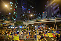 Pro-democracy protesters block the road in Admiralty, on the second day of the mass civil disobedience campaign Occupy Hong Kong, Admiralty, Hong Kong, China, 30 September 2014. The movement is also being dubbed the 'umbrella revolution' after the versatile umbrellas used to shield protesters from rain, sun - and police pepper spray.