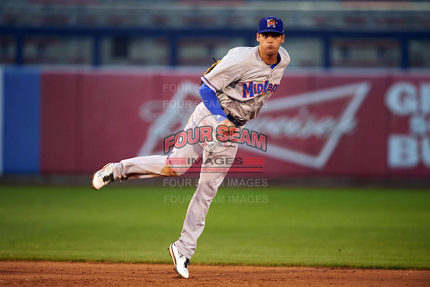 Midland RockHounds shortstop Chad Pinder (2) follows through on a throw to first after fielding a ground ball during a game against the Tulsa Drillers on June 2, 2015 at Oneok Field in Tulsa, Oklahoma.  Midland defeated Tulsa 6-5.  (Mike Janes/Four Seam Images)