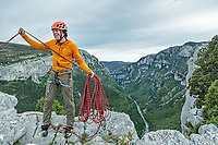 Climber coils ropes on top of a cliff, Verdon Gorge, France