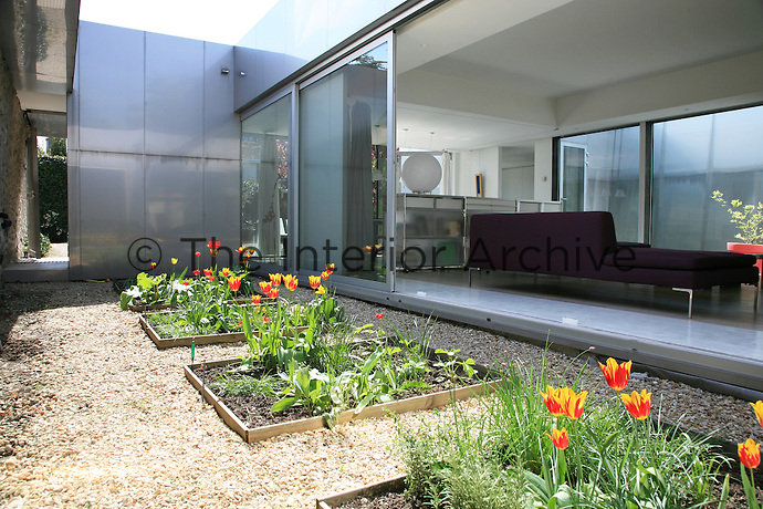 Sliding glass panels are set into the east and west facing walls and open onto gardens and terraces