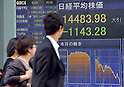 May 23, 2013, Tokyo, Japan - Passersby give glances at the stock price board as Japan stock prices plunged 7.3 percent, the biggest one-day drop in two years, on the Tokyo Stock Exchange market on Thursday, May 23, 2013. The Nikkei ended at 14,483.98, 1,143.28 points lower in the 11th-largest point drop on record.  (Photo by Natsuki Sakai/AFLO)